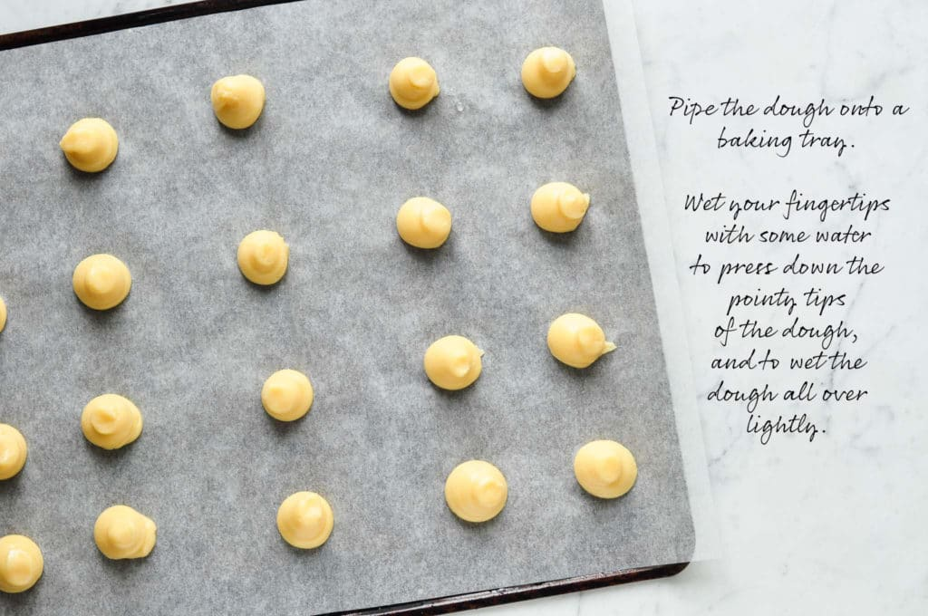 How to make chouquettes (french cream puffs). Pipe the choux pastry onto a baking tray.