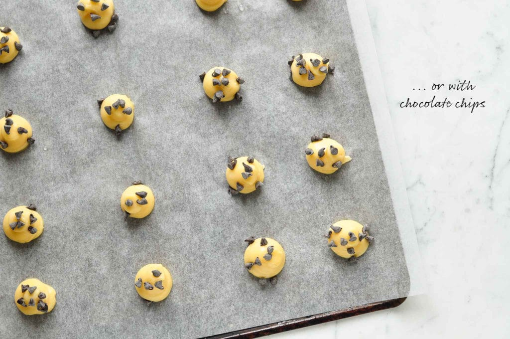 How to make chouquettes (French cream puffs). Sprinkle the dough with chocolate chips.