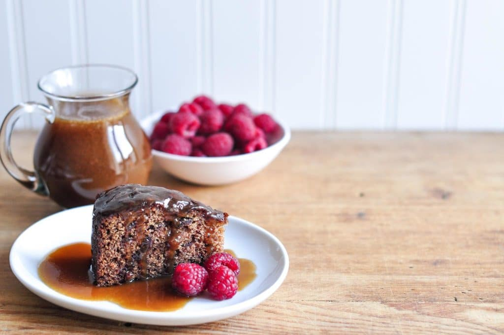 Slice of sticky date pudding with butterscotch sauce and raspberries