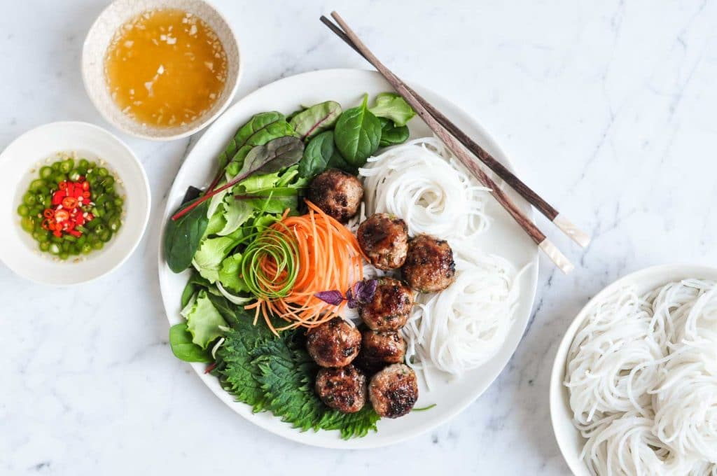 vietnamese pork meatballs on plate with noodles, with plate of fresh noodles to the side
