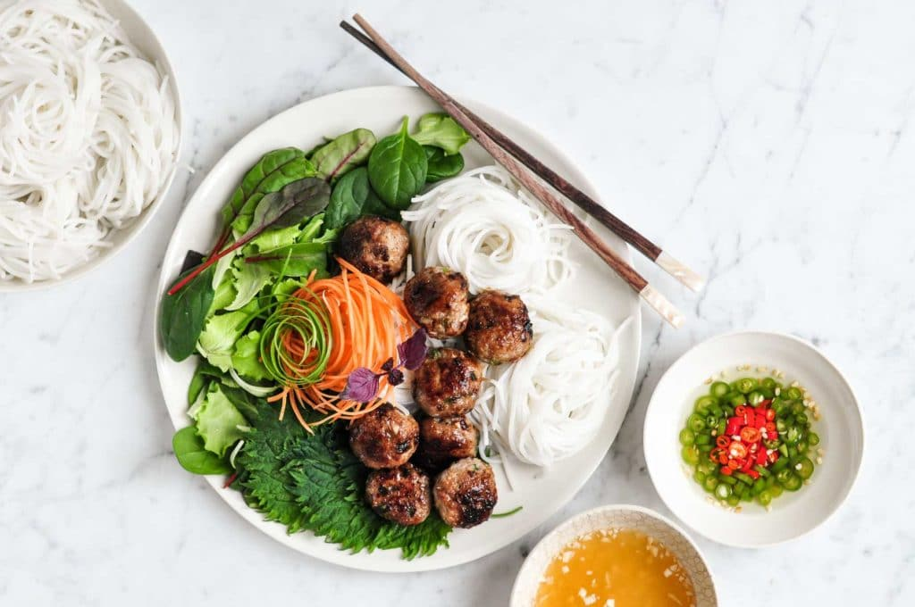 vietnamese pork meatballs on plate with noodles, fresh salad and chopsticks