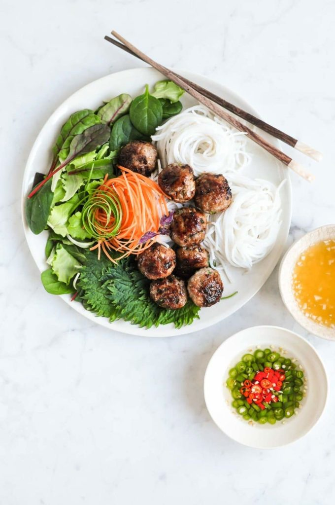 vietnamese pork meatballs on plate with noodles, with small bowl of chopped chillies