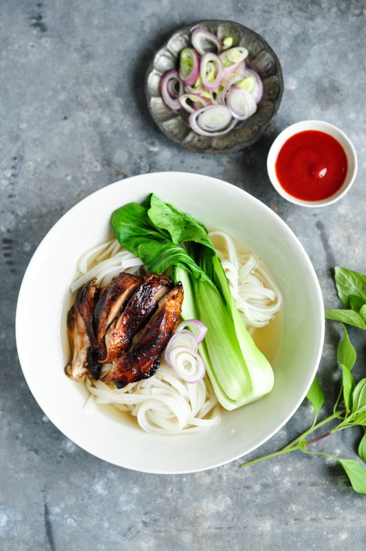 sticky chicken pho with sriracha sauce in bowl