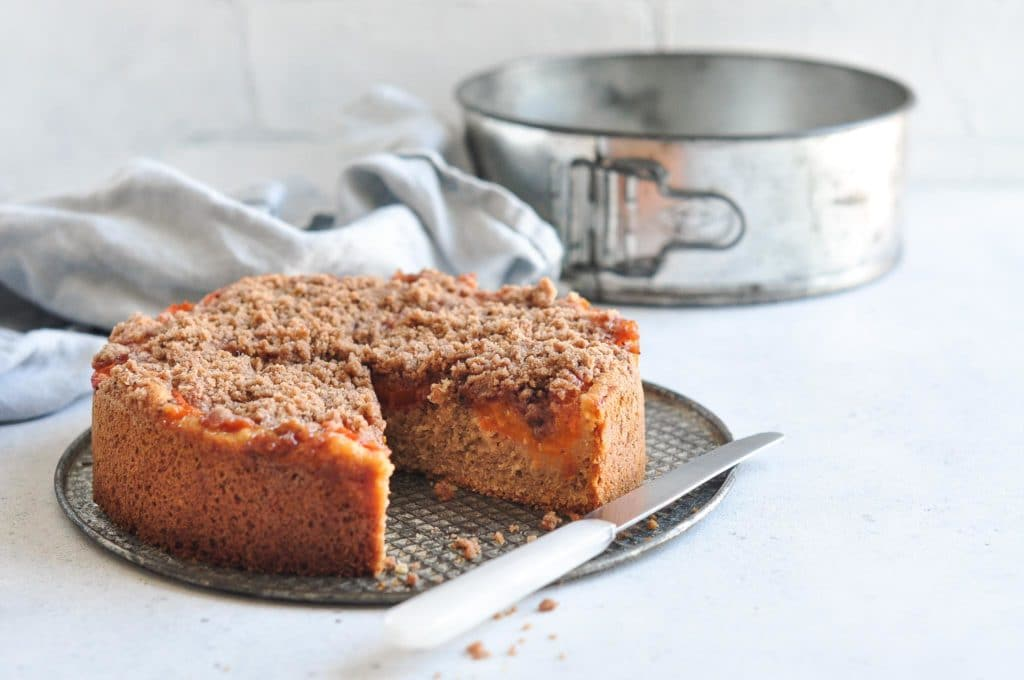 apricot crumble cake on metal tray with white cake knife