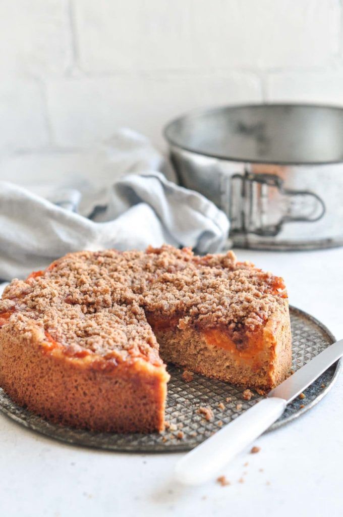 apricot crumble cake on metal tray with vintage cake tin in background