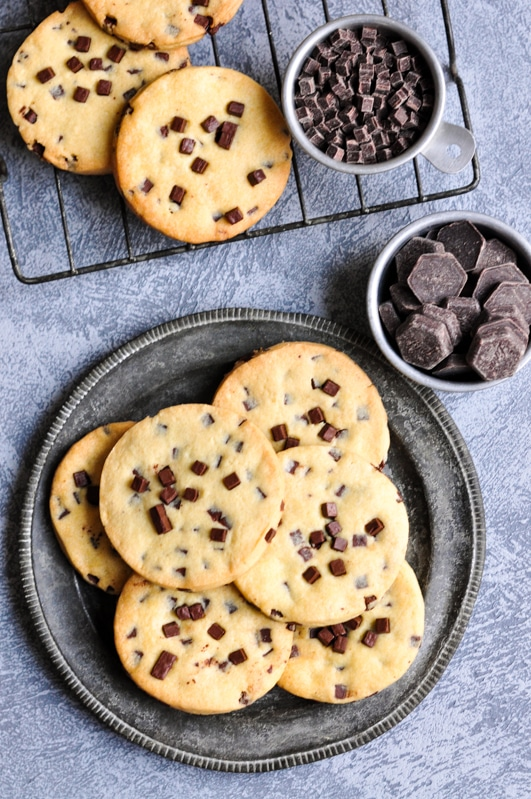 chocolate chip sable cookies on metal plate and wire rack