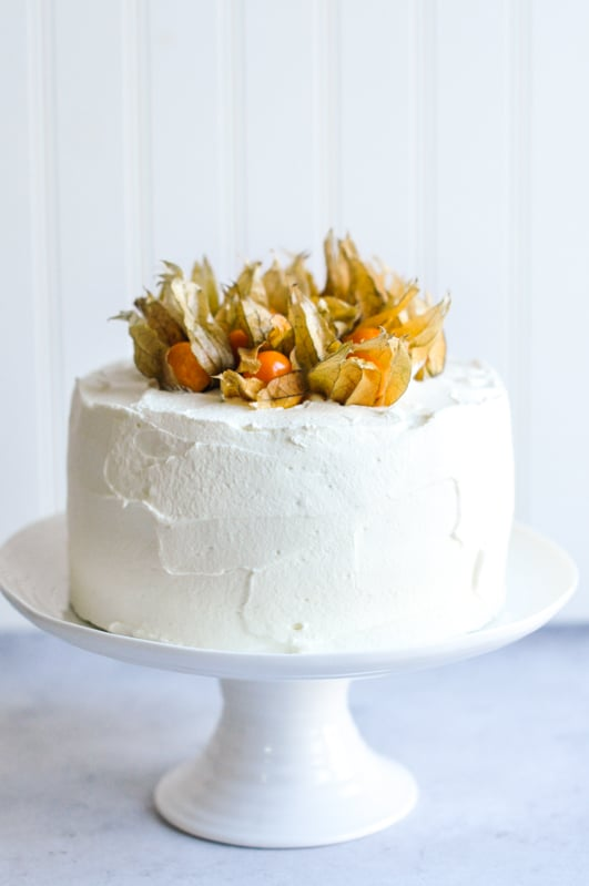 vanilla sponge cake with mascarpone frosting on cake stand with physalis berries