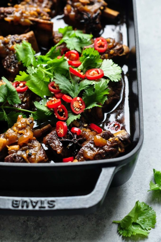 asian beef short ribs in black casserole tray with cilantro and chilli