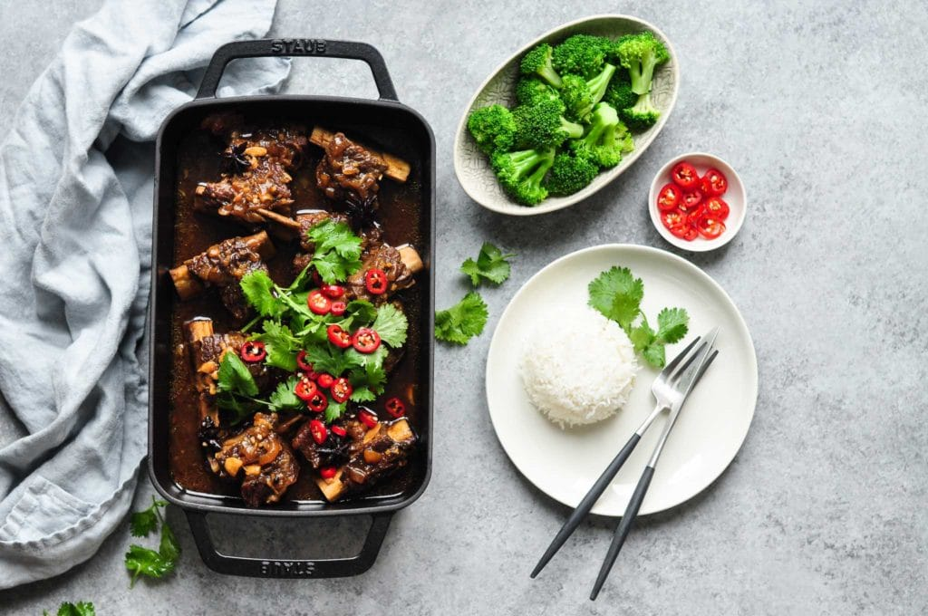 asian braised beef short ribs with a plate of steamed rice and broccoli