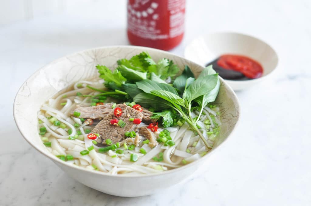 bowl of beef pho with bottle or sriracha hot sauce in background