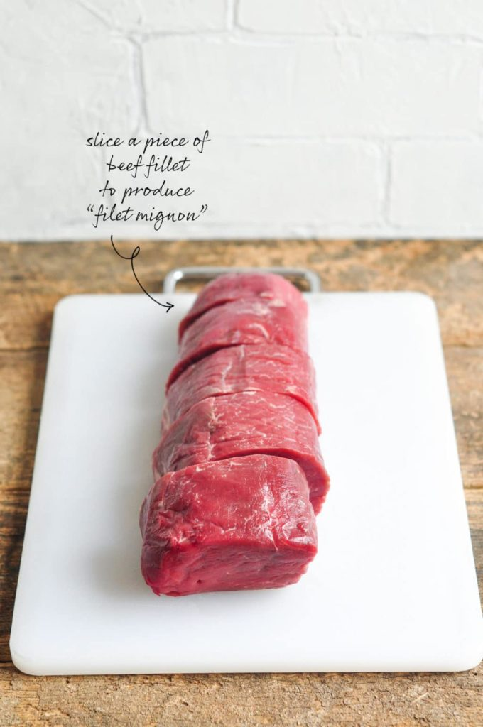 beef fillet sliced into filet mignon on white chopping board