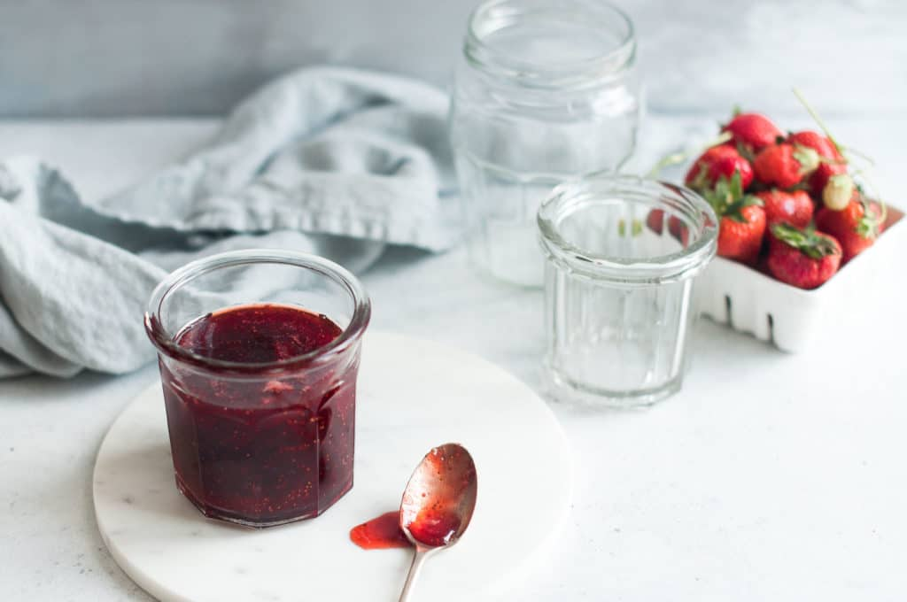 glass of strawberry jam on marble plate