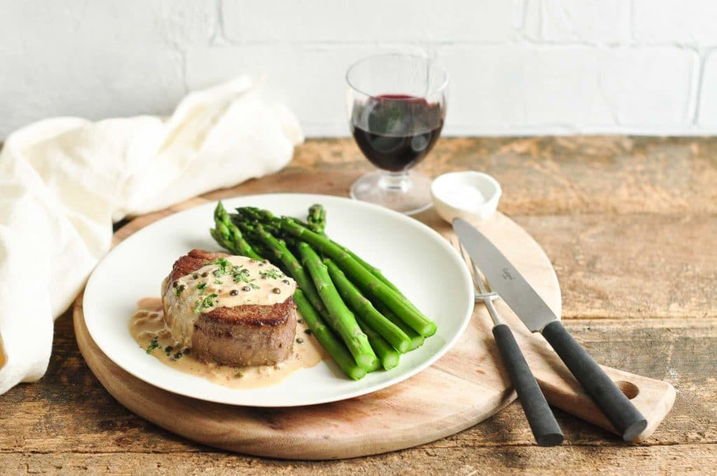 steak with peppercorn sauce on plate with asparagus and glass of red wine
