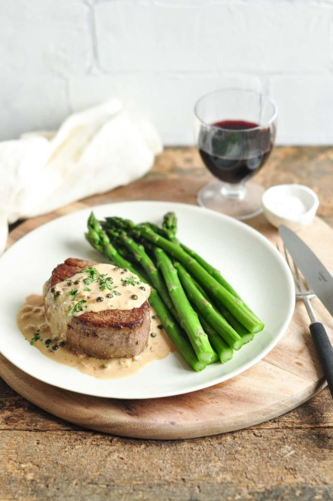 steak with peppercorn sauce on plate with asparagus and black cutlery