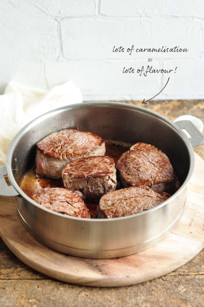 filet mignon seared in frying pan on wooden board