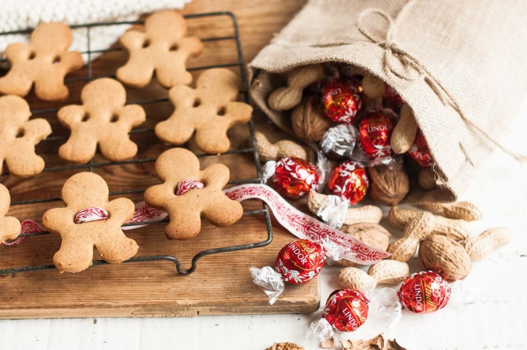 gingerbread men on wire rack with bag of walnuts and peanuts