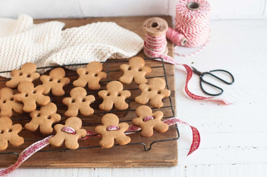 gingerbread man cookies on wire rack with wooden board underneath