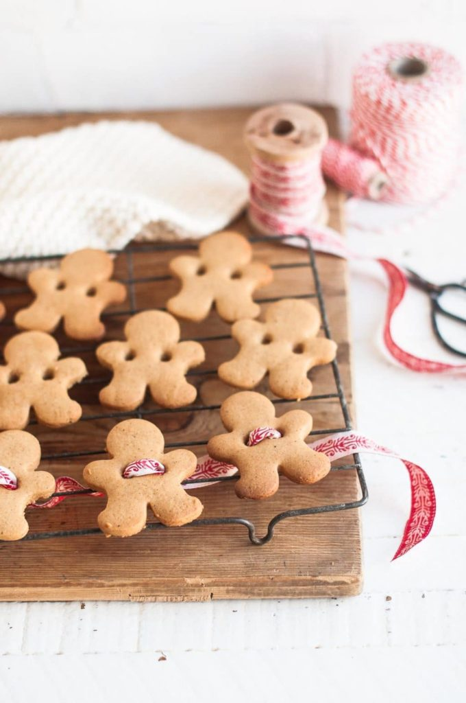 gingerbread man cookies on wire rack with red Christmas ribbon