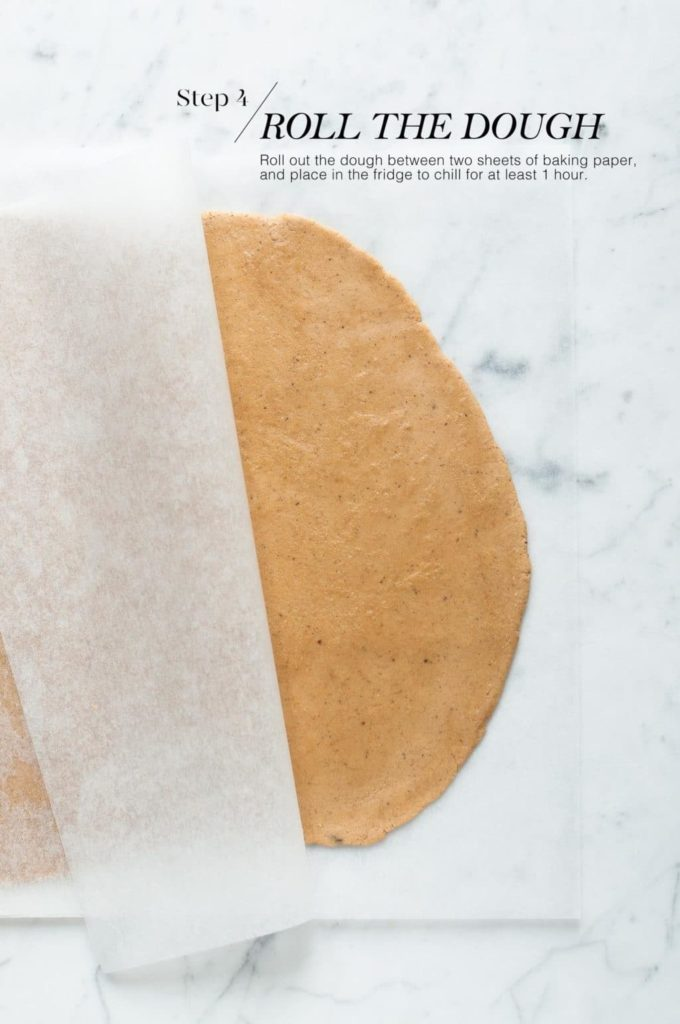 how to make gingerbread man cookies | rolled out gingerbread dough between two sheets of baking paper