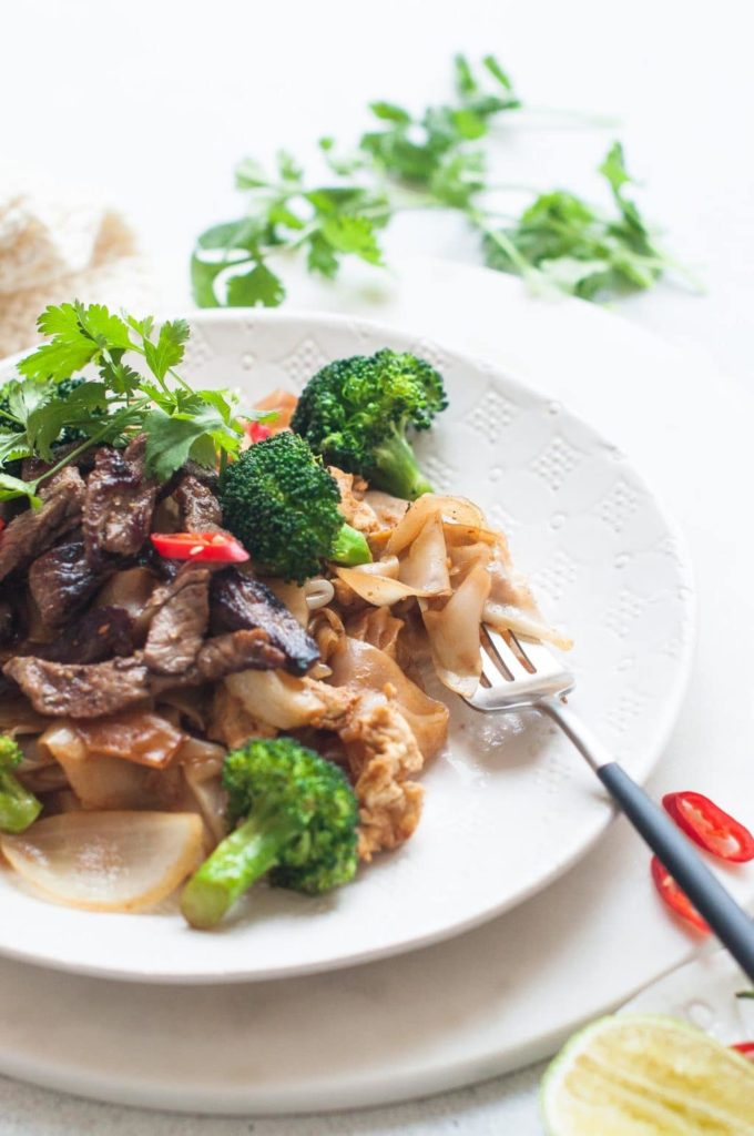 fork of thai stir fried noodles, pad see ew, on white plate