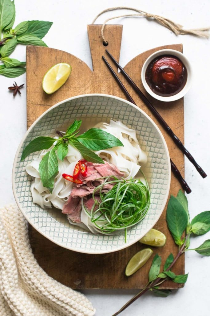 vietnamese beef pho in noodle bowl with slices of beef, herbs and chillies