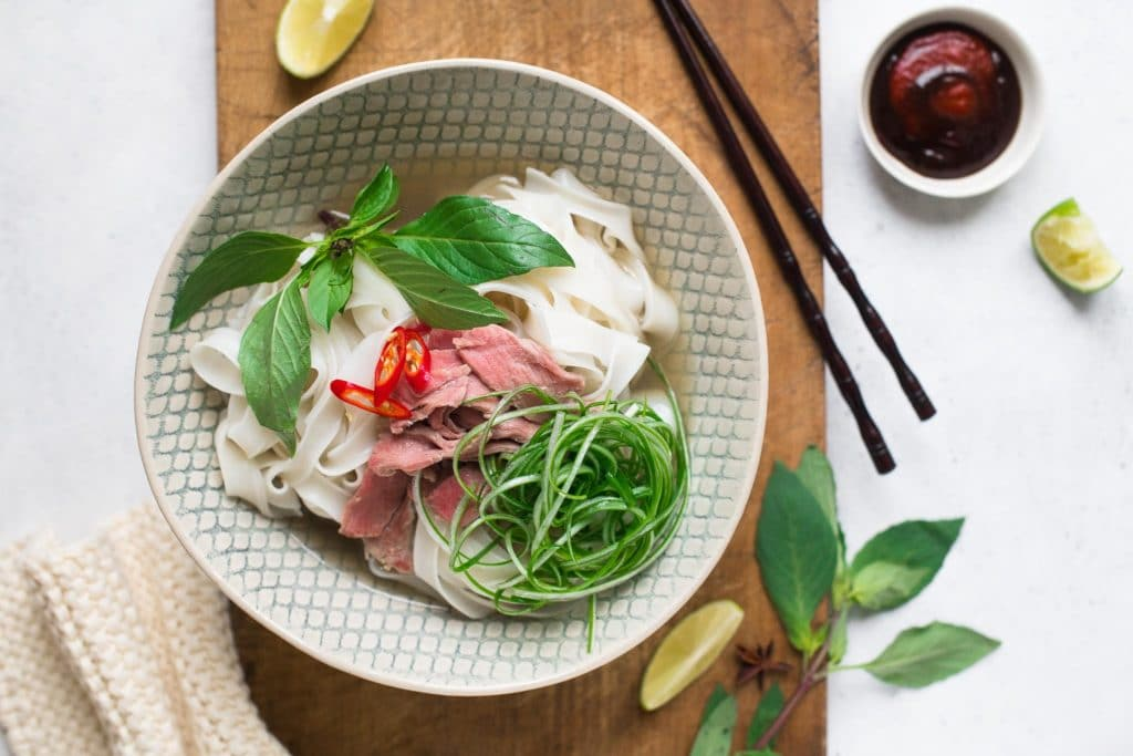 beef pho recipe, noodles with sliced beef and herbs in large bowl