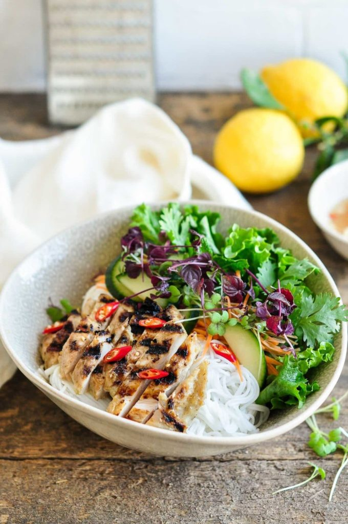 large bowl with sliced grilled chicken on rice vermicelli noodles with herbs and salad