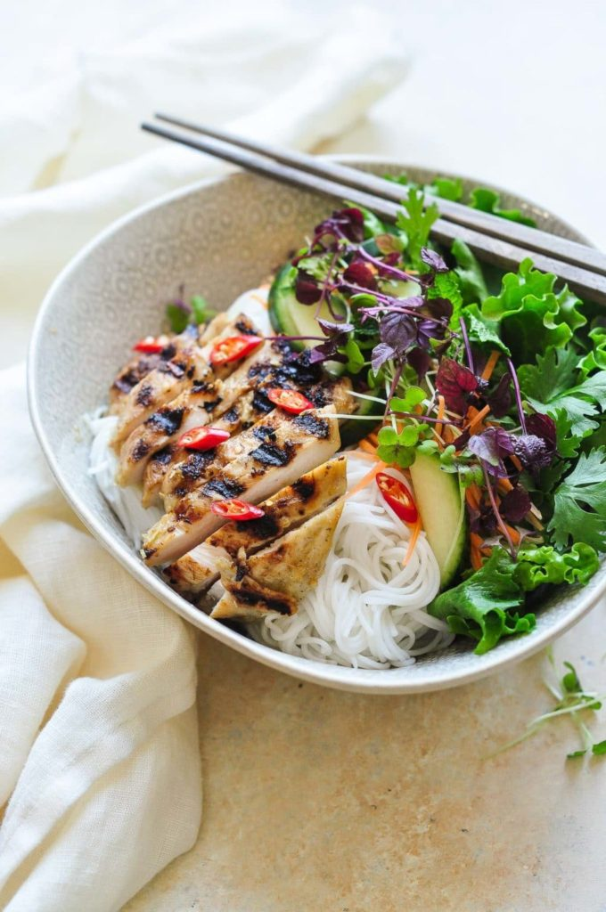 sliced grilled lemongrass chicken in a bowl filled with noodles, salad and herbs with chopsticks on top