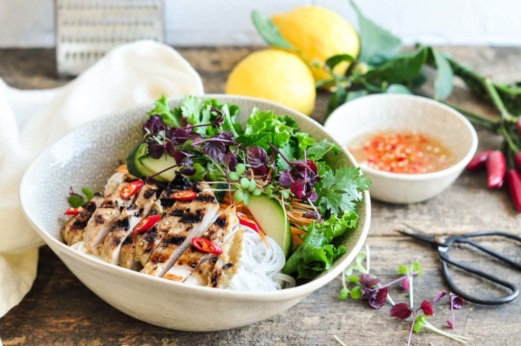 bowl with lemongrass chicken sliced with a noodle salad with a bowl of nuoc cham dipping sauce