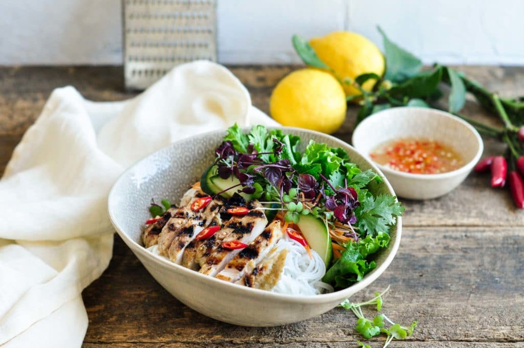 bowl filled with vietnamese noodle salad with sliced grilled chicken on top next to white tea towel
