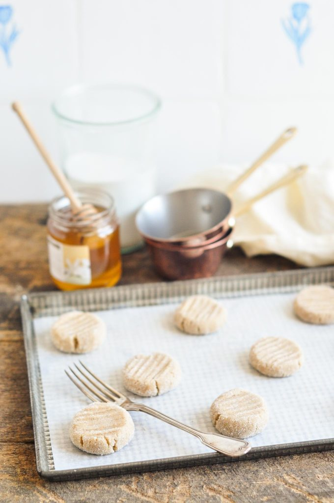 unbaked ginger snap cookies on baking tray with vintage fork