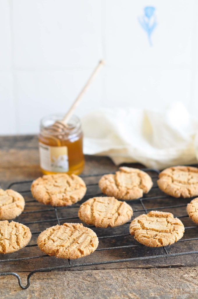 gingernut biscuits on wire rack with jar of honey in background