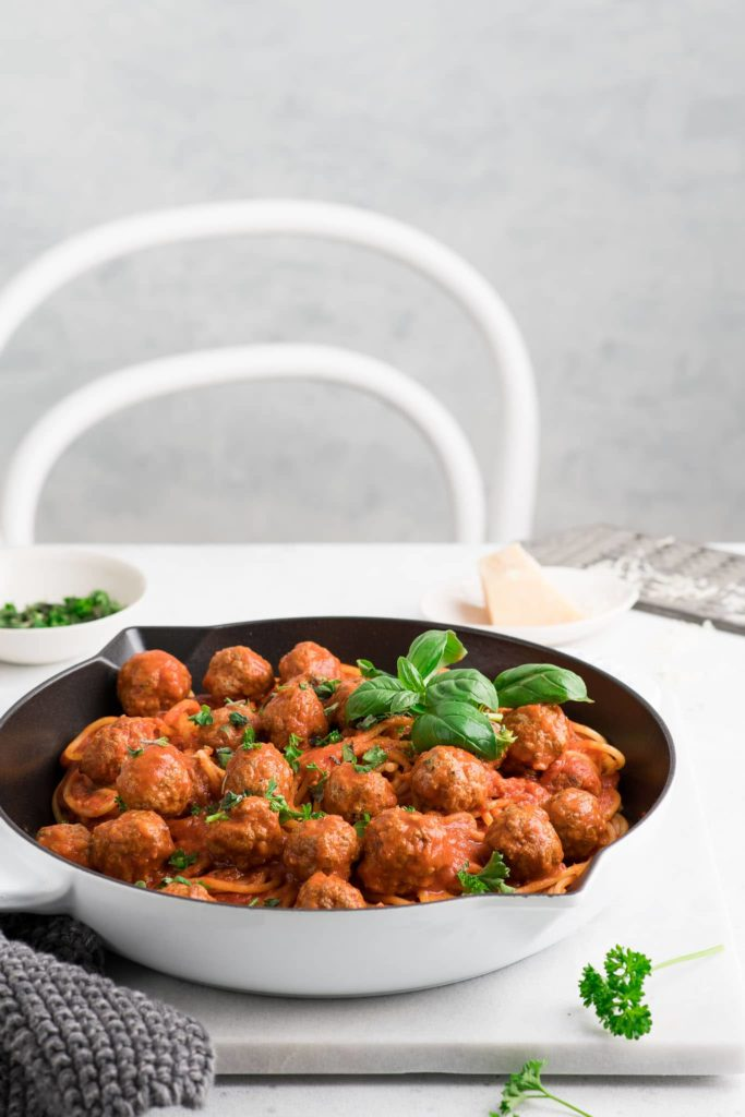 spaghetti and meatballs in white skillet garnished with basil