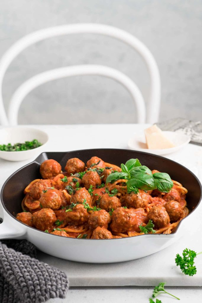 spaghetti and meatballs garnished with fresh herbs