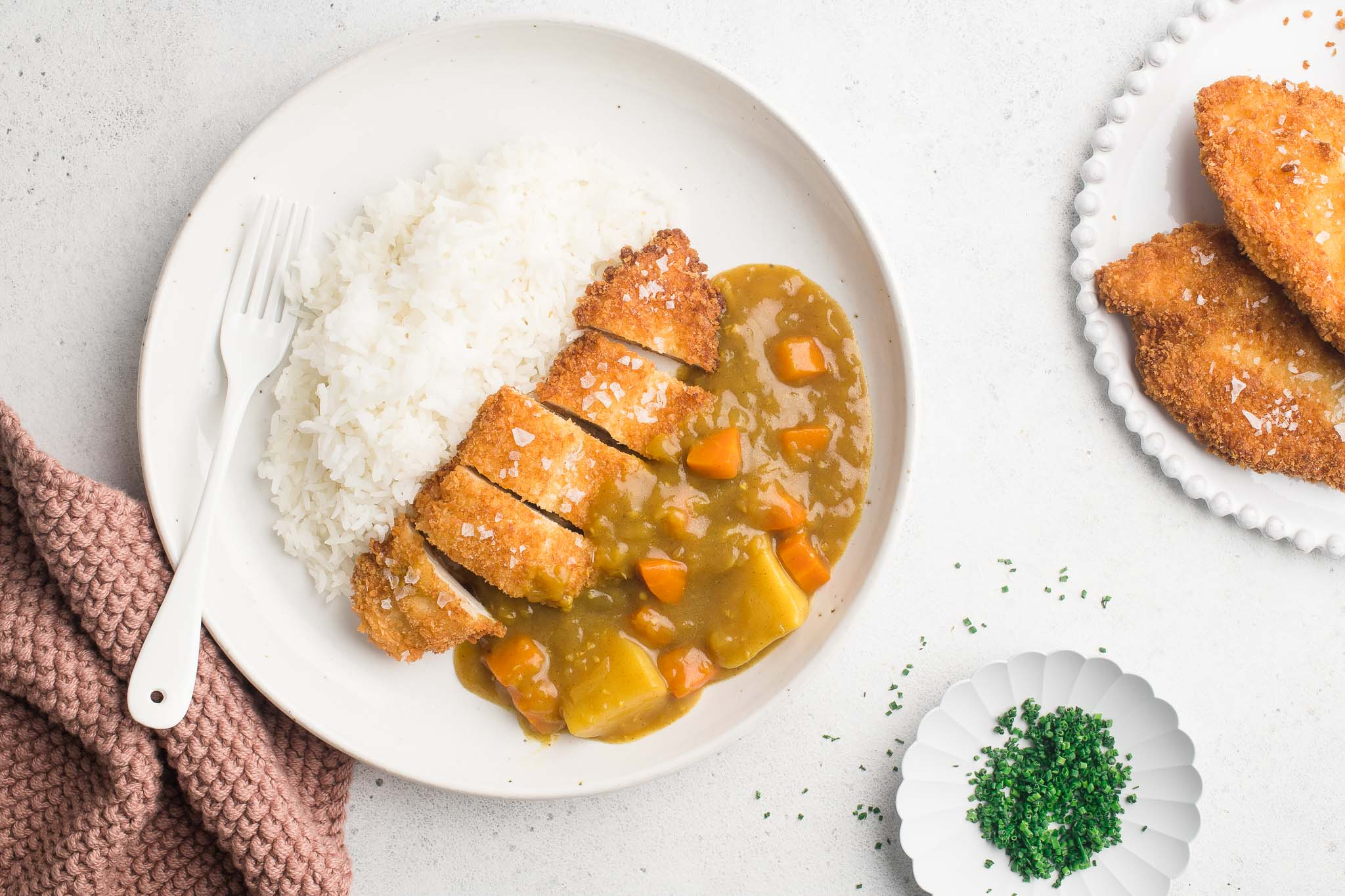 chicken katsu curry on white plate with rice