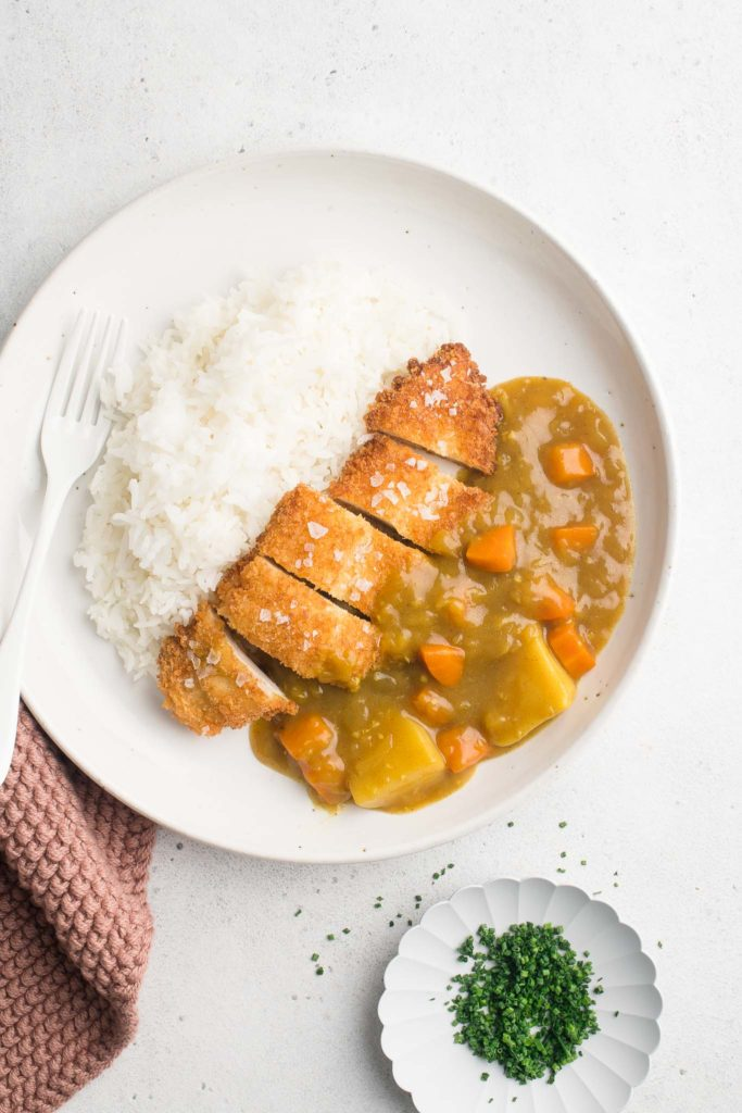 chicken katsu curry with rice on white plate with fork