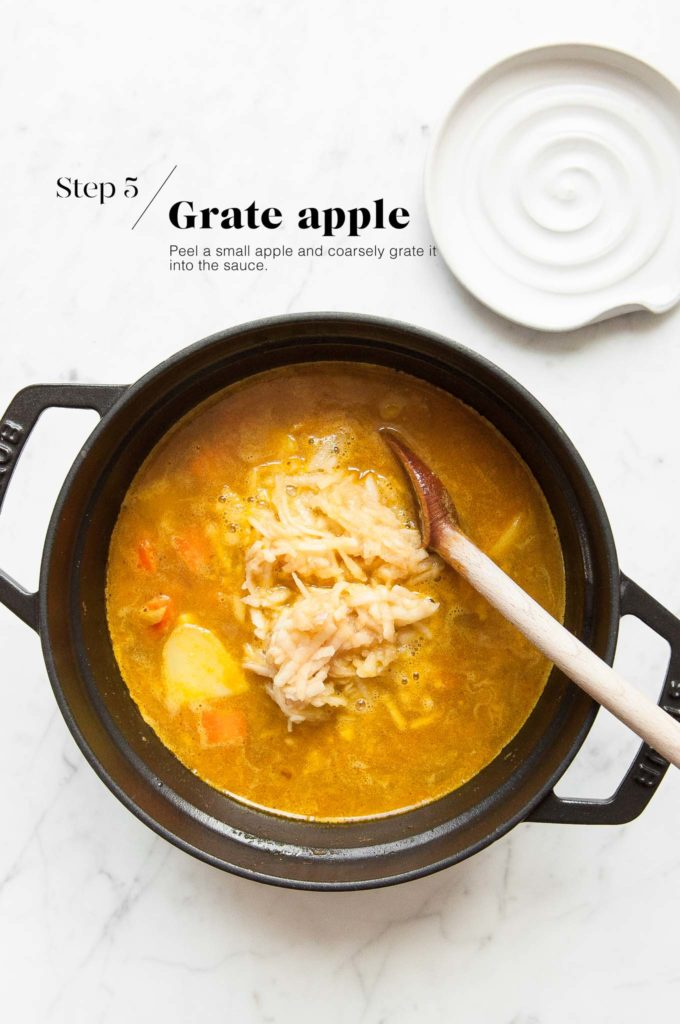adding grated apple to katsu curry in cast iron pot