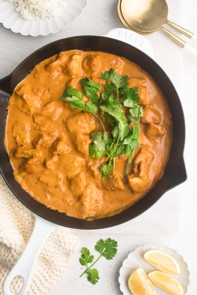 butter chicken in pan with sliced lemons