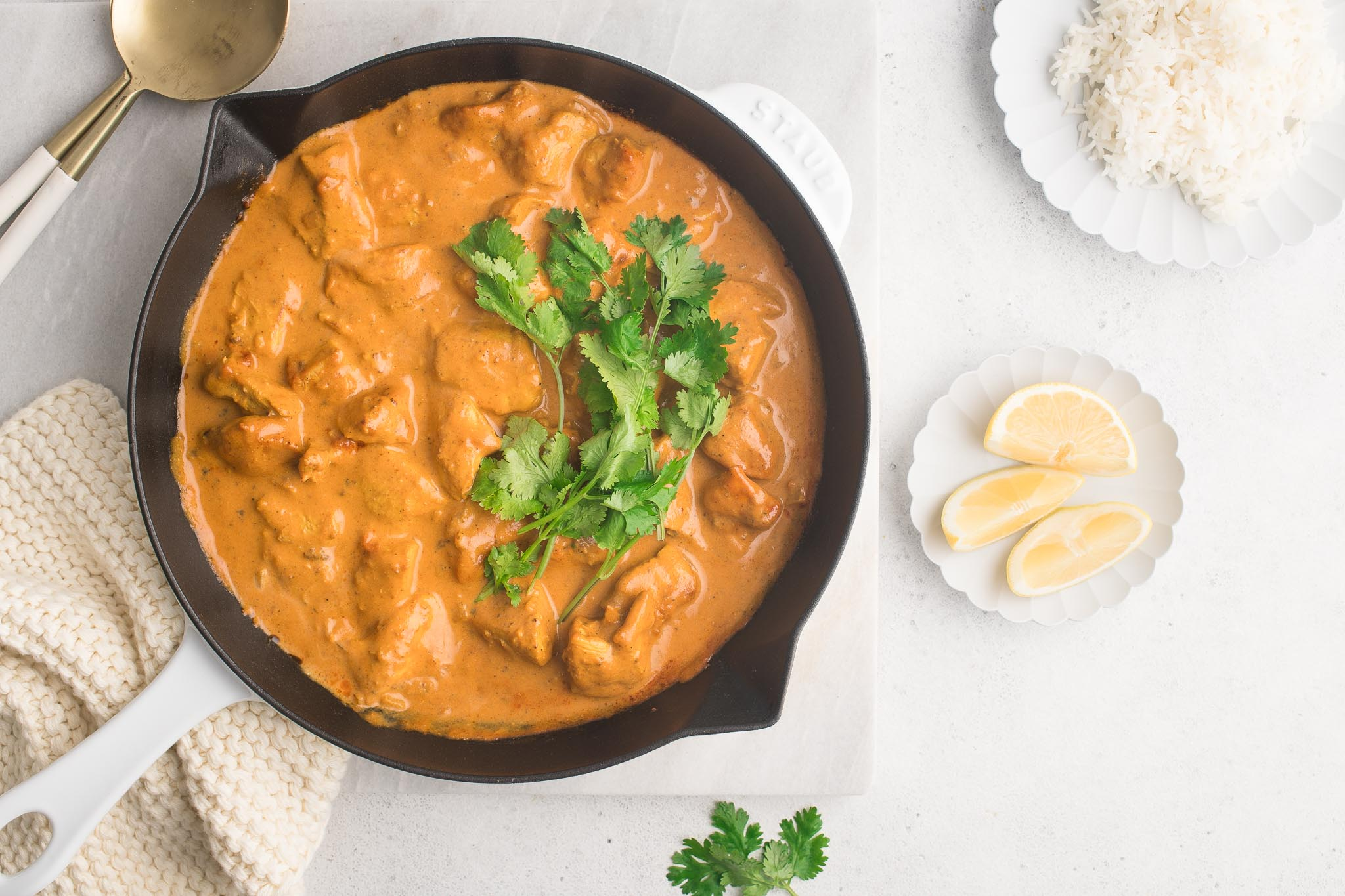 butter chicken in white cast iron pan