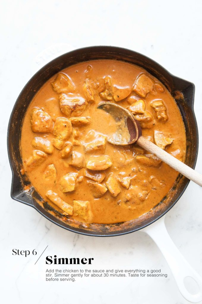 butter chicken simmering in cast iron pan