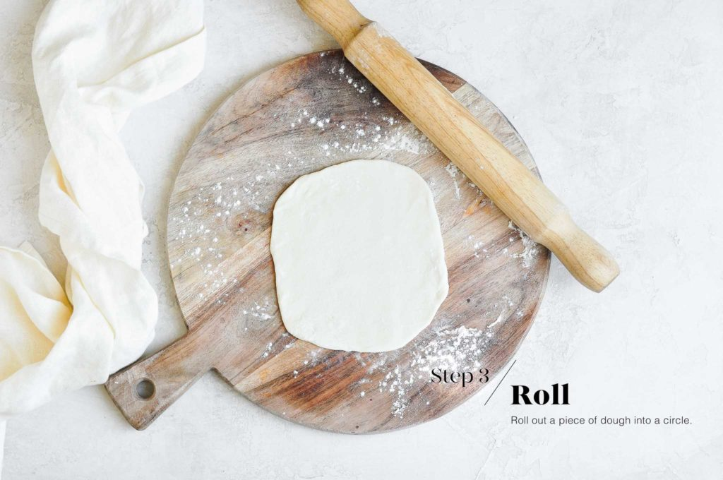rolled out dough for scallion pancakes on wooden board
