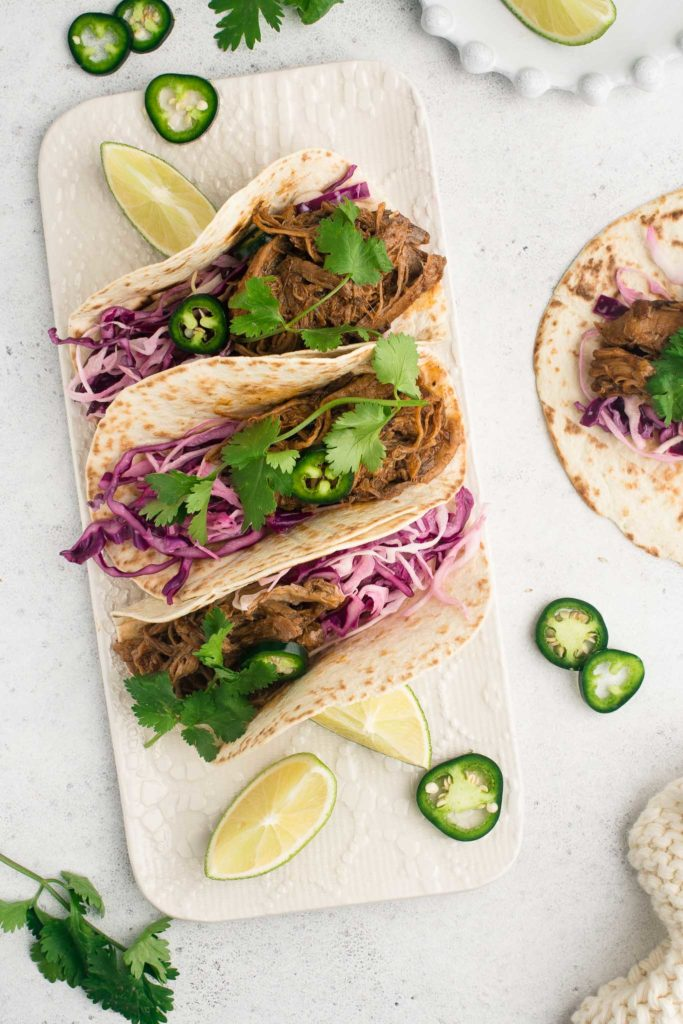 pulled pork tacos with fresh herbs on white plate